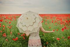 Женщина в маках field держать цветок и зонтик мака Стоковое фото RF