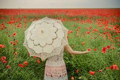 Женщина в маках field держать цветок и зонтик мака Стоковые Фото