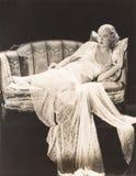 Женщина в мантии шнурка lounging на софе Стоковые Изображения