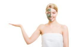 Женщина в маске грязи глины на владениях стороны раскрывает ладонь Стоковая Фотография