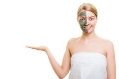 Женщина в маске грязи глины на владениях стороны раскрывает ладонь Стоковое фото RF
