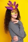 Женщина в маске масленицы с пером, красивым портретом девушки на желтой предпосылке цвета, длинном вьющиеся волосы Стоковое Изображение RF
