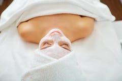 Женщина в маске на стороне в салоне красоты курорта стоковое фото rf