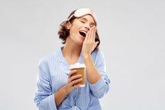 Женщина в маске пижамы и глаза с кофе зевая стоковая фотография rf