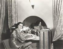 Женщина в металлическом платье сидя на ее таблице шлихты Стоковая Фотография