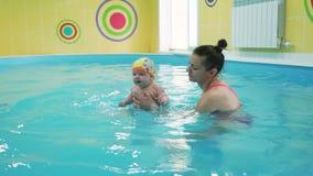 Женщина в младенце преподавательства swimwear как поплавать видеоматериал