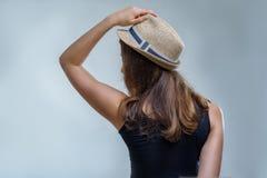 Женщина в модной шляпе и черной рубашке представляя в половинном повороте от задней части стильно на серой предпосылке в студии стоковое фото