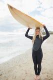 Женщина в мокрой одежде держа surfboard надземный на пляже Стоковая Фотография