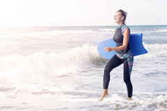 Женщина в мокрой одежде и заплывание всходят на борт идти на пляж Стоковая Фотография
