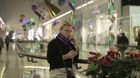 Женщина в моле говоря на телефоне сток-видео