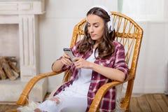 Женщина в наушниках используя smartphone дома Стоковые Фотографии RF