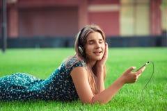 Женщина в наушниках слушая музыку усмехаясь с закрытыми глазами лежа вниз стоковая фотография rf