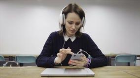 Женщина в наушниках слегка ударяет умный телефон акции видеоматериалы