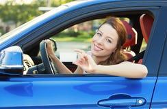 Женщина в новом автомобиле показывая пустую лицензию водителей стоковое фото rf
