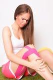 Женщина в ноге боли связанной тесьмой удерживанием раненой стоковая фотография rf