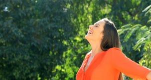 Женщина в оранжевом дыша свежем воздухе в парке видеоматериал