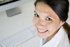 Женщина в офисах усмехается стоковая фотография