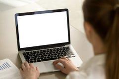 Женщина в офисе работая на компьтер-книжке с экраном модель-макета пустым стоковые изображения rf