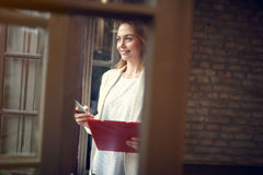Женщина в офисе с телефоном в руках Стоковое Фото