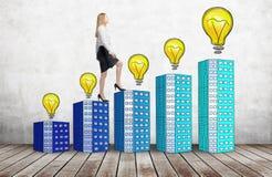 Женщина в официально одеждах идет вверх использовать лестницы которые сделаны домов с лампочками Концепция новых идей и успеха Стоковые Изображения RF