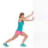 Женщина в одеждах спорт нажимая белую стену Стоковые Изображения RF