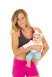 Женщина в одежде фитнеса стоя с младенцем стоковые изображения
