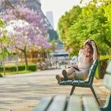 Женщина в Париже, читая книгу около Эйфелевой башни стоковые фото