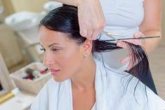 Женщина в парикмахерах имея волосы быть отрезанным не доходя стоковое фото rf