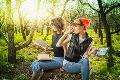 Женщина в парке внешнем с таблеткой и книгой Стоковые Изображения RF