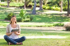 Женщина в парке используя ее компьютер таблетки Стоковая Фотография RF