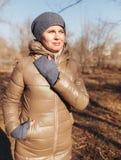 Женщина в парке осени Держит левую руку о шеи стоковое фото rf