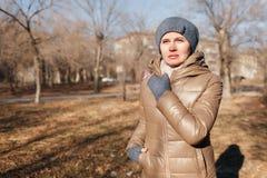 Женщина в парке осени Держит левую руку о шеи стоковые фото