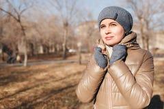 Женщина в парке осени Обе руки держат о шеи стоковые фотографии rf