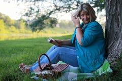 Женщина в парке с книгой на траве Стоковые Фотографии RF