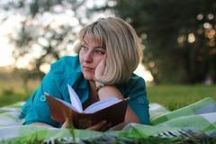 Женщина в парке с книгой на траве Стоковая Фотография