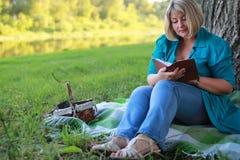 Женщина в парке с книгой на траве Стоковая Фотография RF
