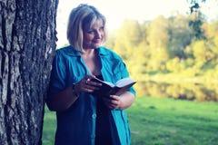Женщина в парке с книгой на траве Стоковое Фото