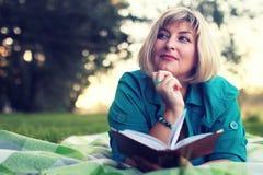 Женщина в парке с книгой на траве Стоковое фото RF