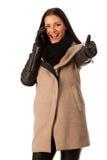 Женщина в пальто зимы стоя уверенно с большим пальцем руки вверх говоря Стоковое Изображение RF