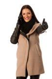 Женщина в пальто зимы стоя уверенно с большим пальцем руки вверх говоря Стоковые Изображения RF