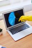 Женщина в перчатках пылясь с малой компьтер-книжкой веника Стоковые Фото