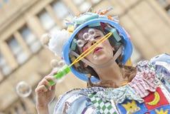 Женщина в пестротканом платье дует пузыри мыла на Манчестере d Стоковая Фотография RF