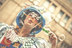 Женщина в пестротканом платье дует пузыри мыла на Манчестере d Стоковые Изображения RF