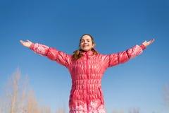 Женщина в пинке приветствуя солнце Стоковые Фотографии RF