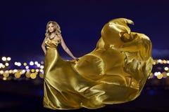 Женщина в платье золота над городом ночи, фотомоделью в длинной золотой мантии, развевая ткани стоковая фотография rf