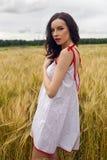 Женщина в платье красного света стоит в поле стоковые фото