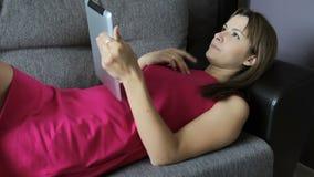 Женщина в платье лежит с таблеткой на софе Ложь на вашей задней части Симпатичная женщина дома сток-видео
