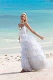 Женщина в платье невесты стоя на море край стоковые фотографии rf