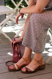 Женщина в платье сидя с ее рукой на ее сумке стоковые изображения rf