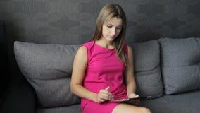 Женщина в платье сидя с таблеткой на кресле Девушка работая на планшете сидя на софе видеоматериал